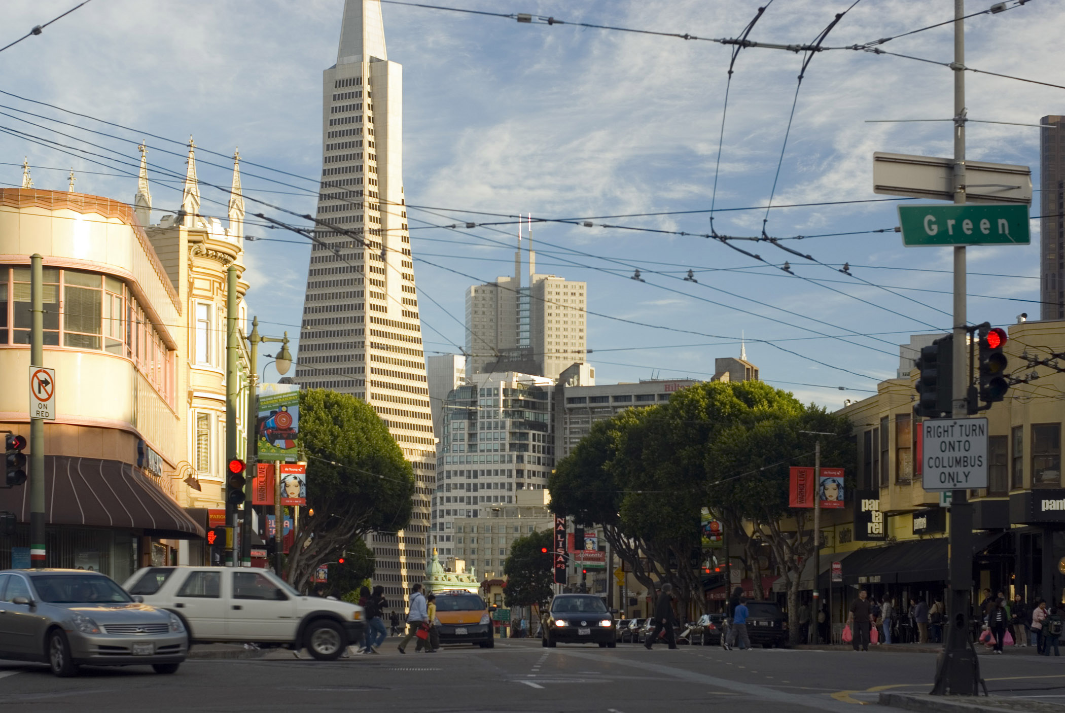 Street level scene of a busy intersection with traffic and pedestrians on Columbus Avenue San Francisco with the Transamerica Pyramid behind