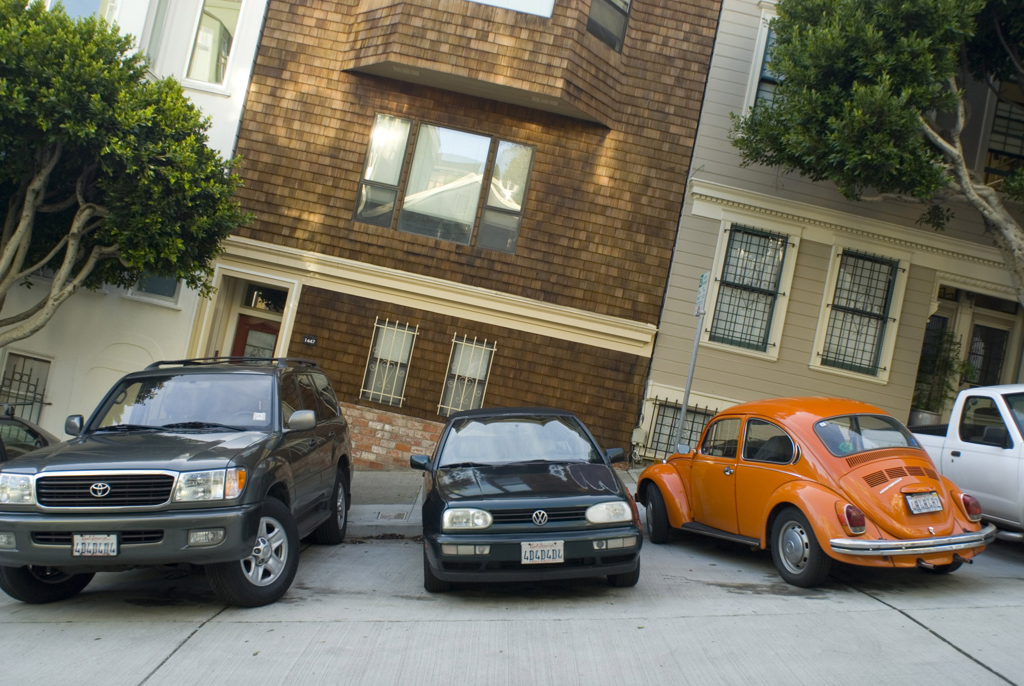 Cars parked side by side in front of residential houses on a steep hill in San Francisco, California, USA