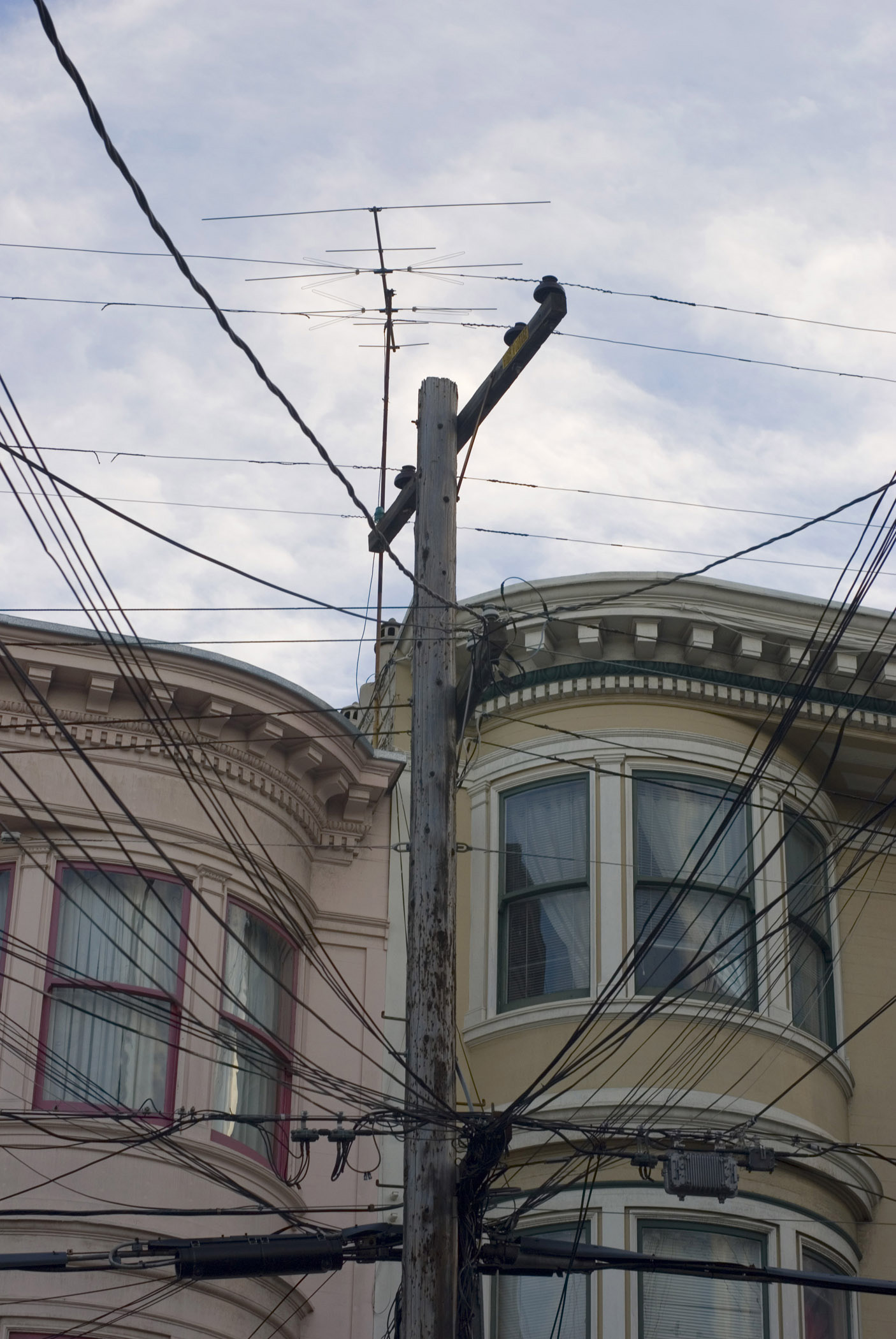 San Francisco architecture with a view of the historical wooden facades of townhouses past a spaghetti junction electricity pole