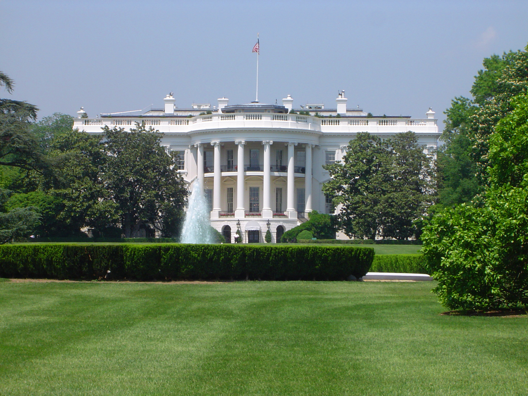 Scenic view of the exterior of the White House, Washington DC viewed across manicured green lawns on a sunny summer day