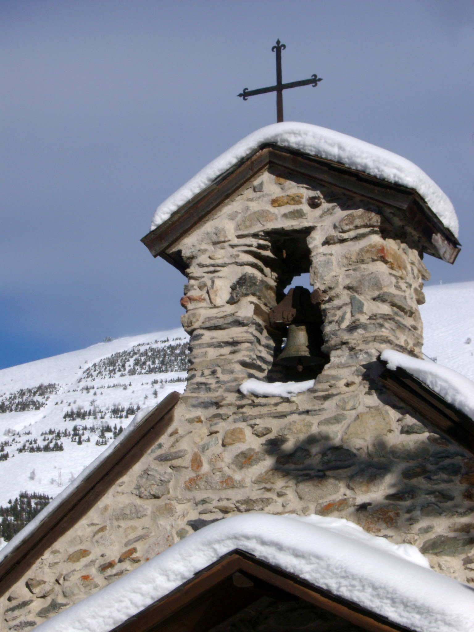 Historic Alpine Church, Covered with Snow, with Vintage Bells and Cross