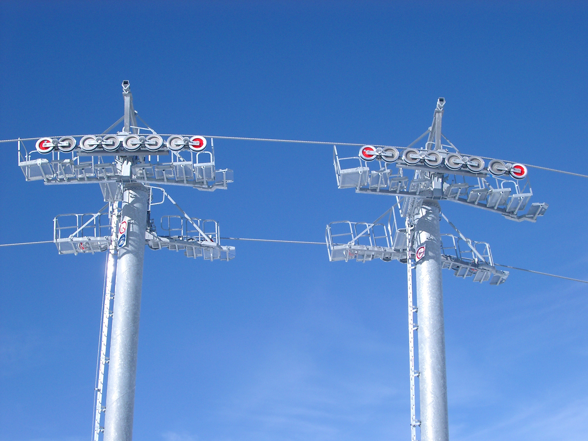Detail of an alpine chair lift showing the towers and cables with the pulleys against a clear blue sunny winter sky