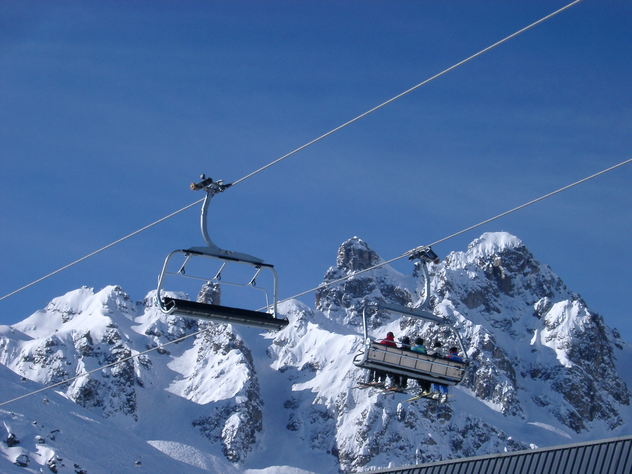 Tourists Riding High Cable Car on a Snow Mountain on Light Blue Sky Background.