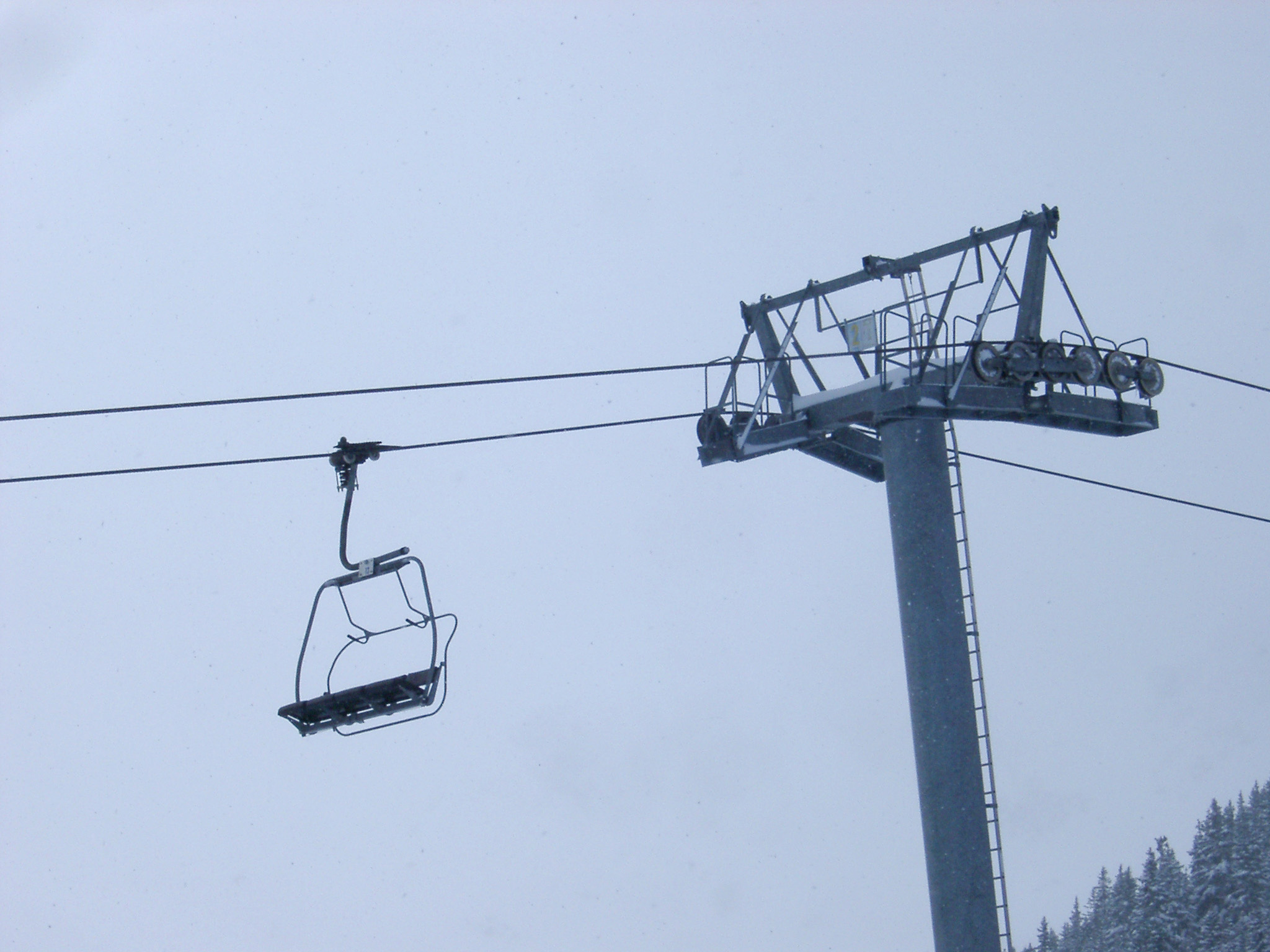 Cable car or Alpine chair lift for taking tourists and skiers to the mountain ski slopes with an empty chair suspended close to a pylon or tower