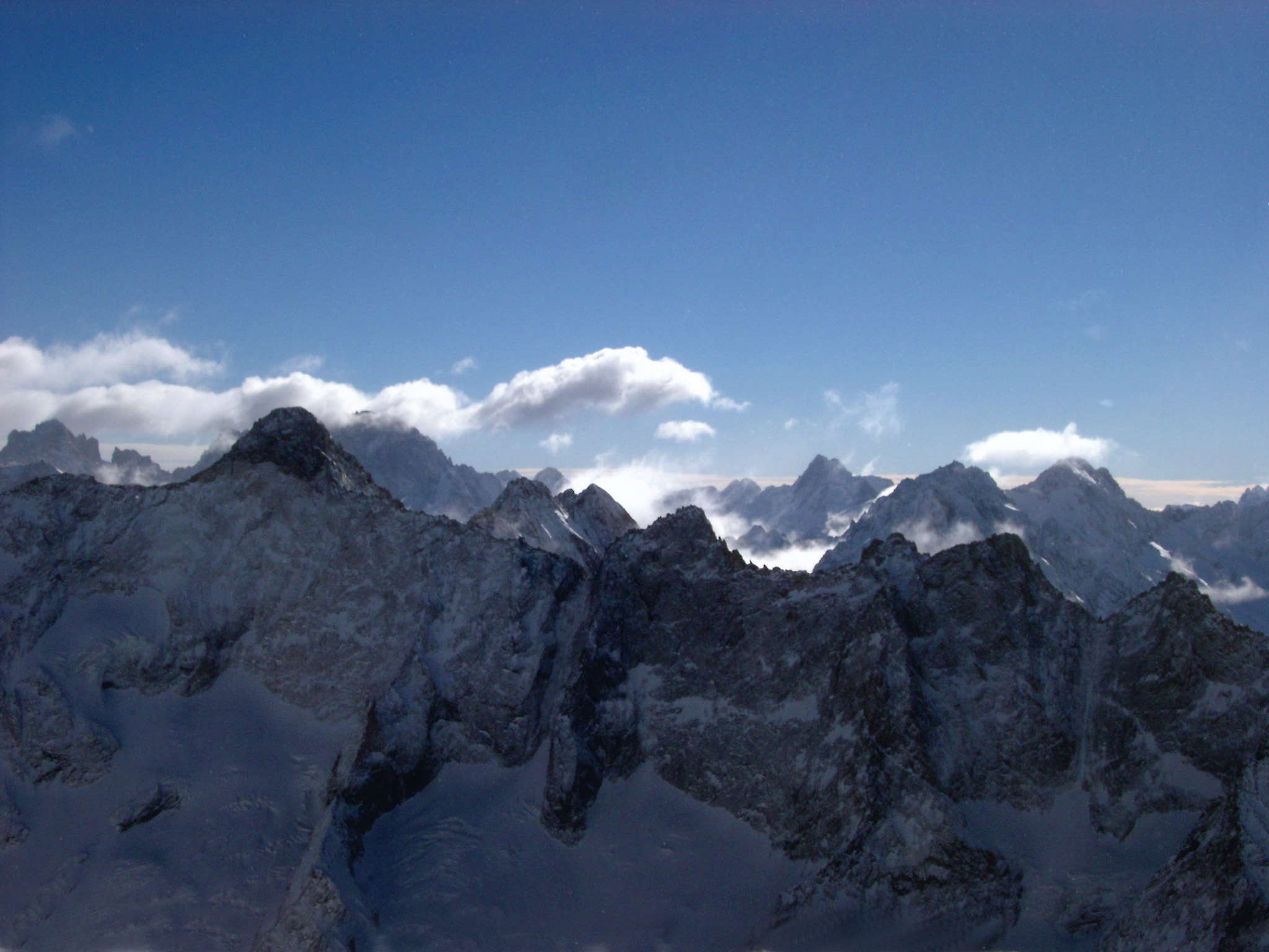 High rugged alpine peaks in France in winter with fluffy white clouds above in a blue sunny sky