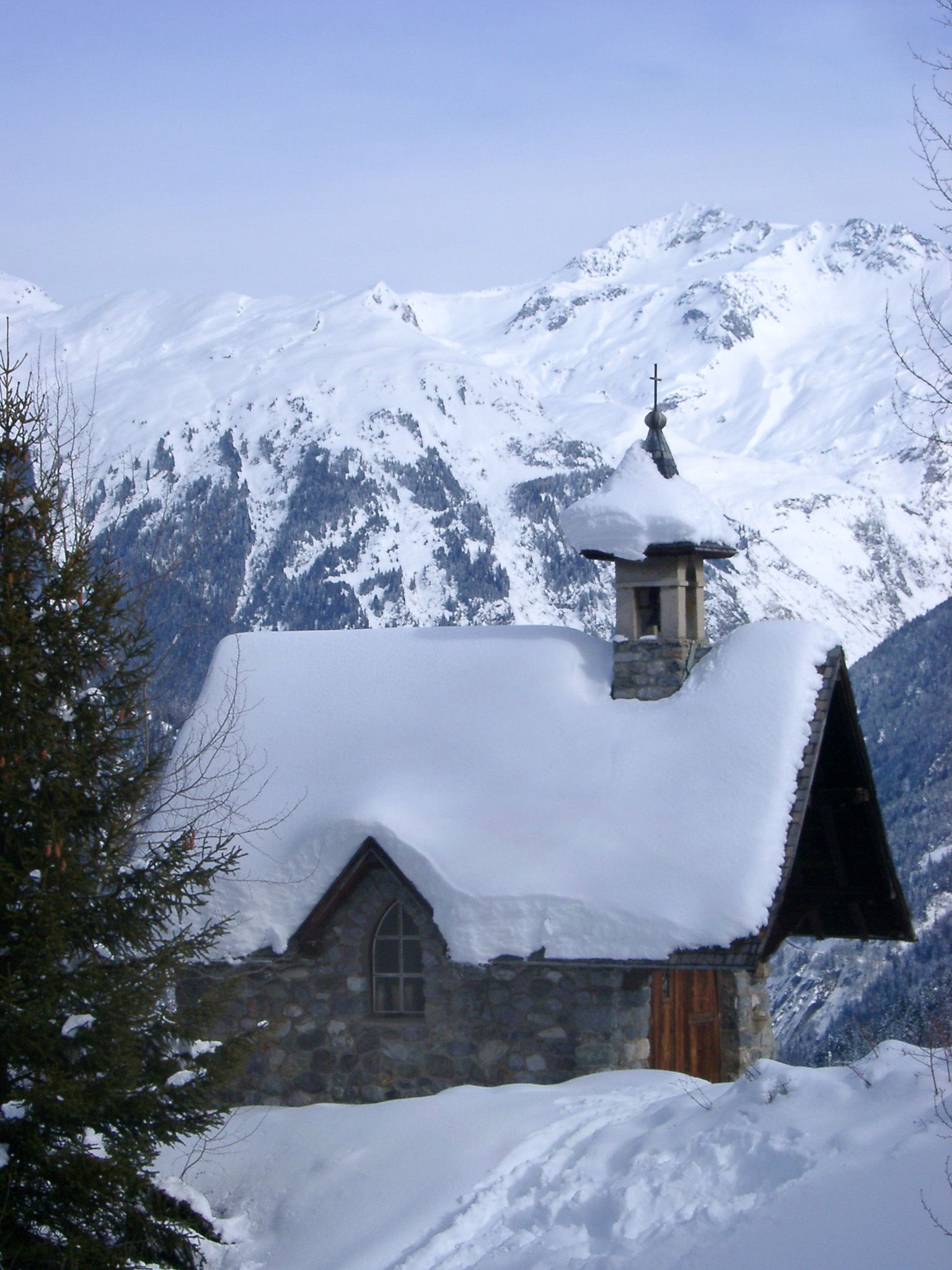 Historic Small Architectural Christian Church Building Filled with Snow, Captured with Huge Mountain on Background During Winter Season.