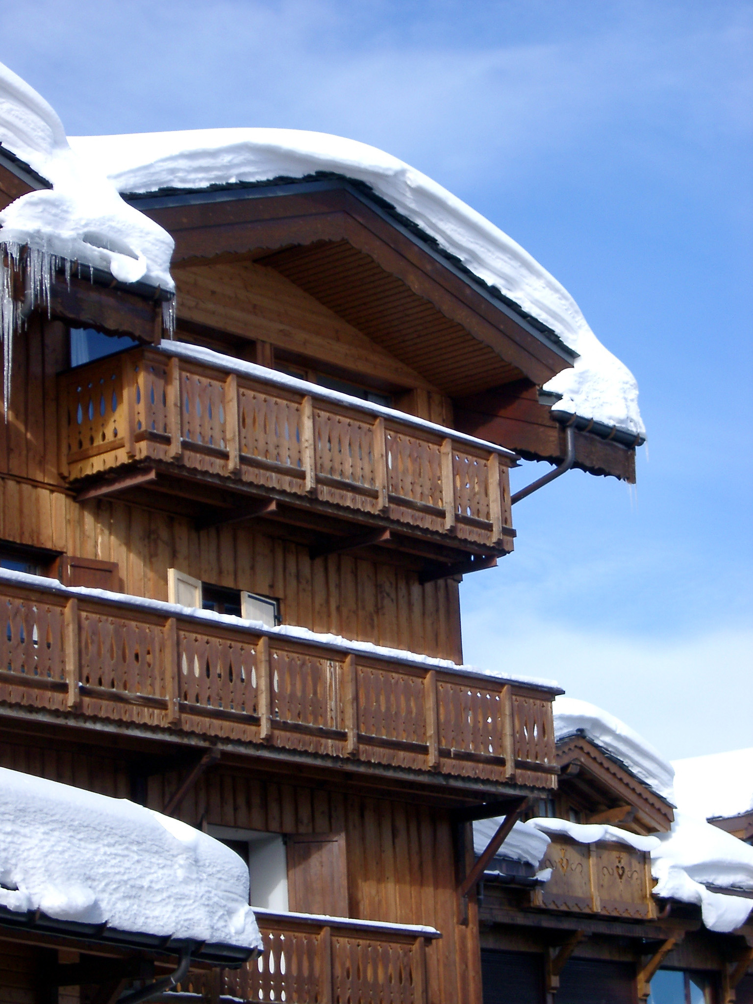 Snow Covering Rooftop of Vintage Wooden Alpine Lodge on Lighter Blue Sky Background.