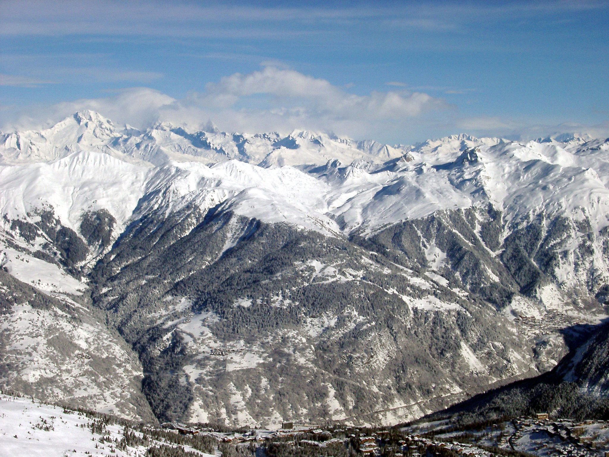 Mountainous winter landscape in France with spectacular rugged mountain ranges covered in snow stretching into the distance under a sunny blue sky