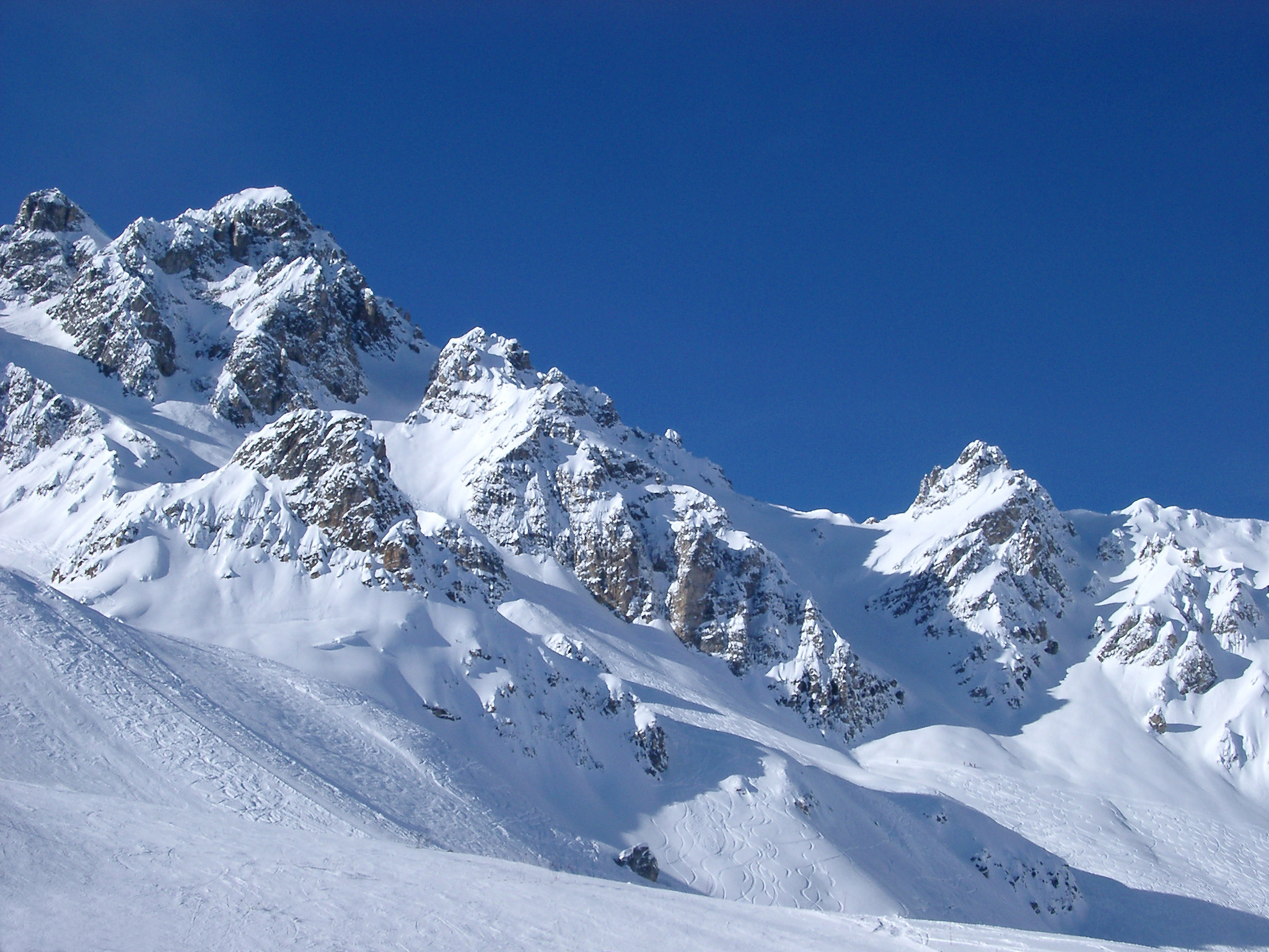 Snow covered rugged mountain peaks in France under a clear crisp blue winter sky in a spectacular landscape