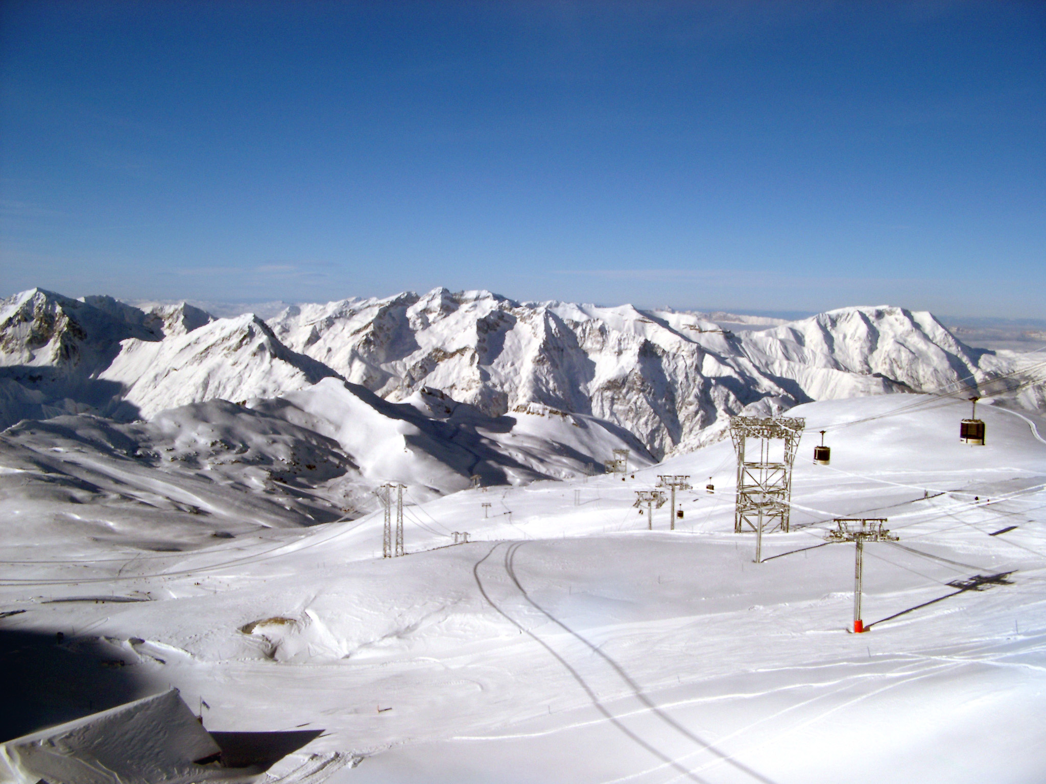 Scenic winter landscape with snow covered mountains and a piste with chair lifts for skiers