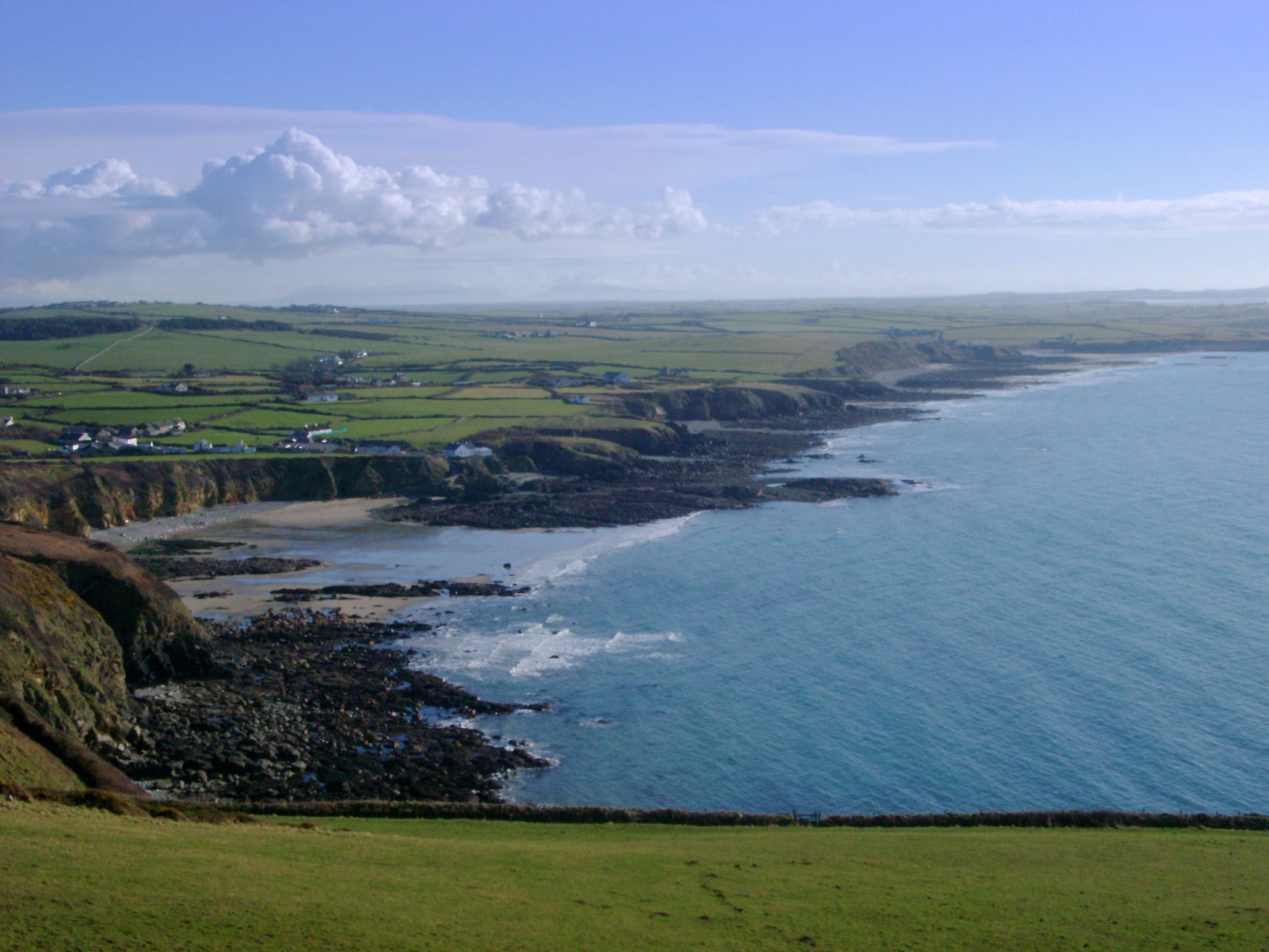 Extensive view of the Anglesey coastline and bay with a calm blue ocean, rocky cliffs and green plateau, Wales, UK