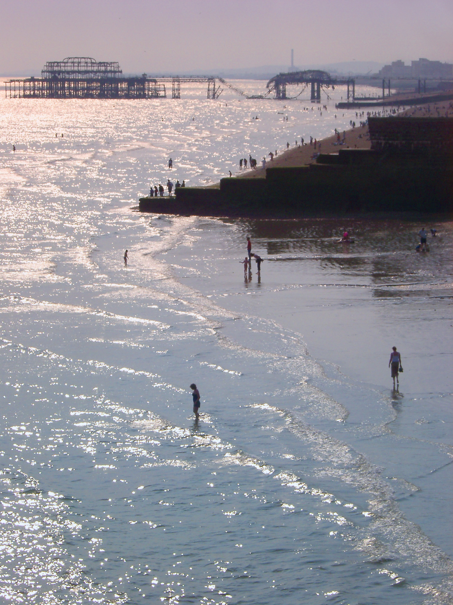 People paddling at Brighton beach with the remnants of the burnt out historical pier visible behind them on a warm summers