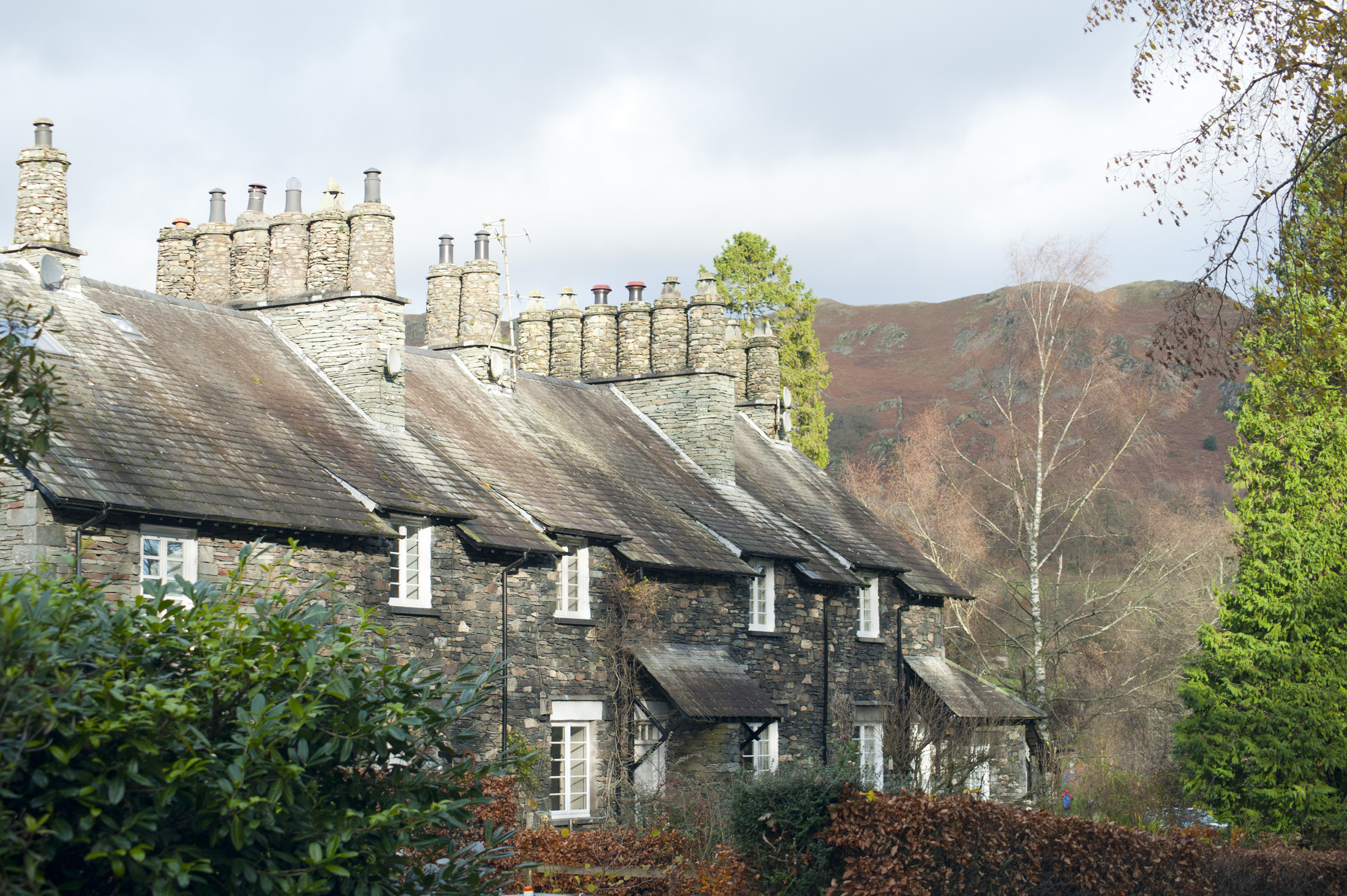 Picturesque row of English stone cottages at Skelwith Bridge in the Lake District in Cumbria with traditional round stone chimney pots