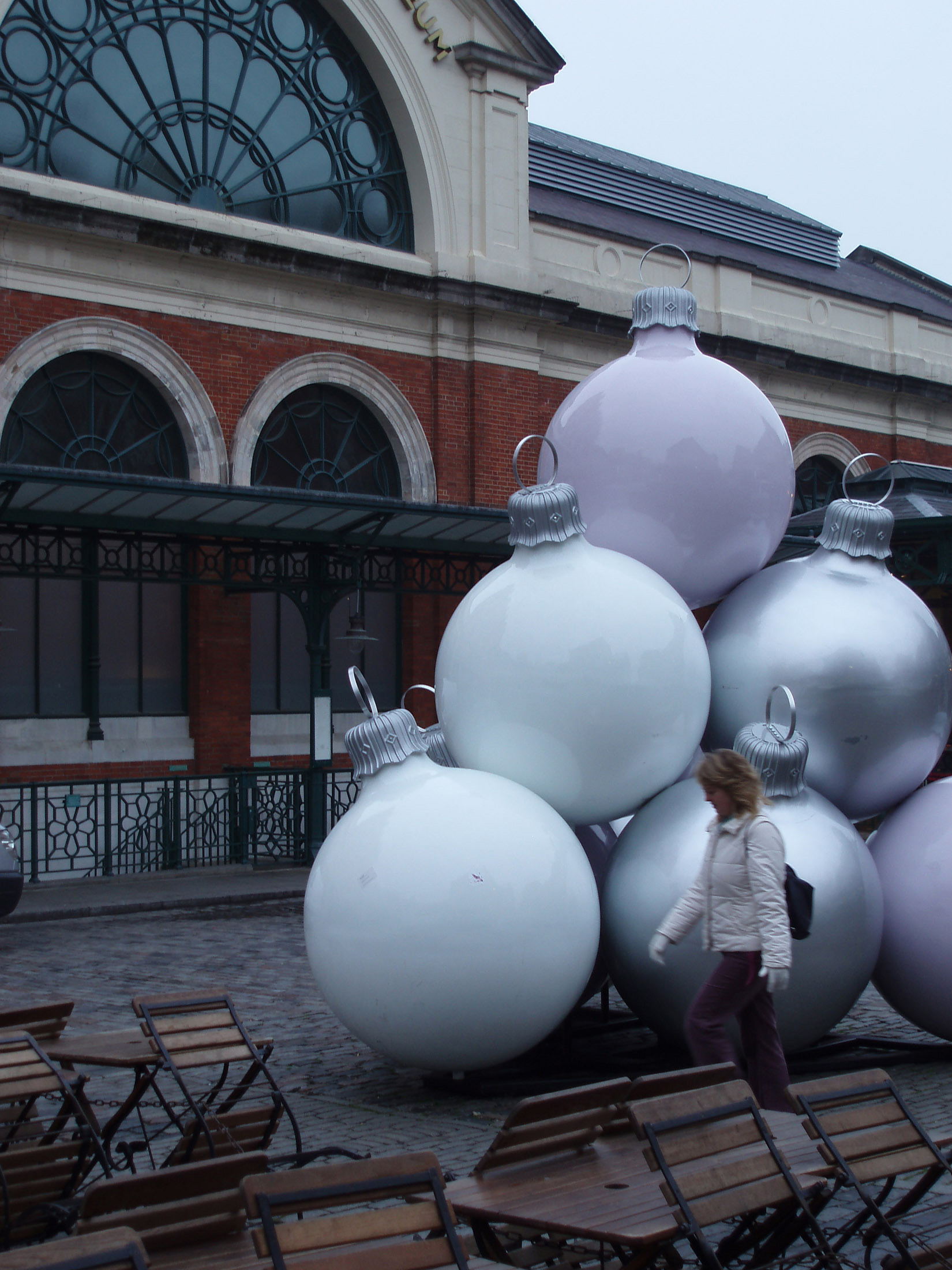 Covent Gardens display of Christmas decorations with a woman walking past a stack of large silver baubles near on open-air restaurant , London, England