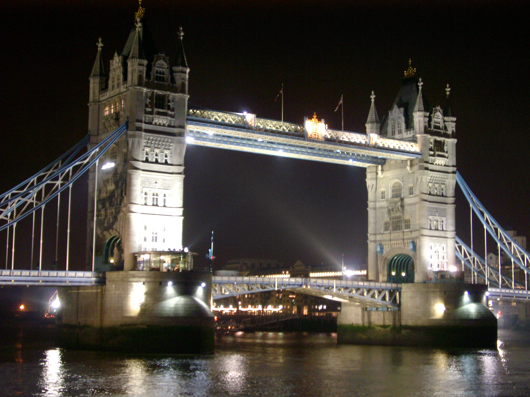 Tower Bridge, London, on the River Thames illuminated at night with the drawbridge down and reflections on the calm water