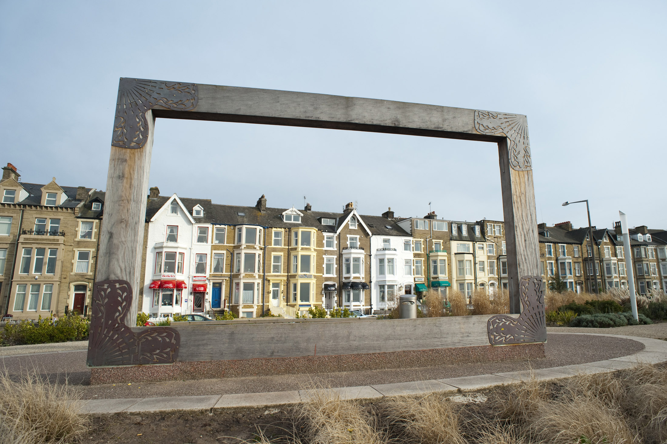 a large wooden picture frame at the west end gardens in morecambe, when viewed from the opposite side allows visitors to frame a bleak vista of morecambe sands