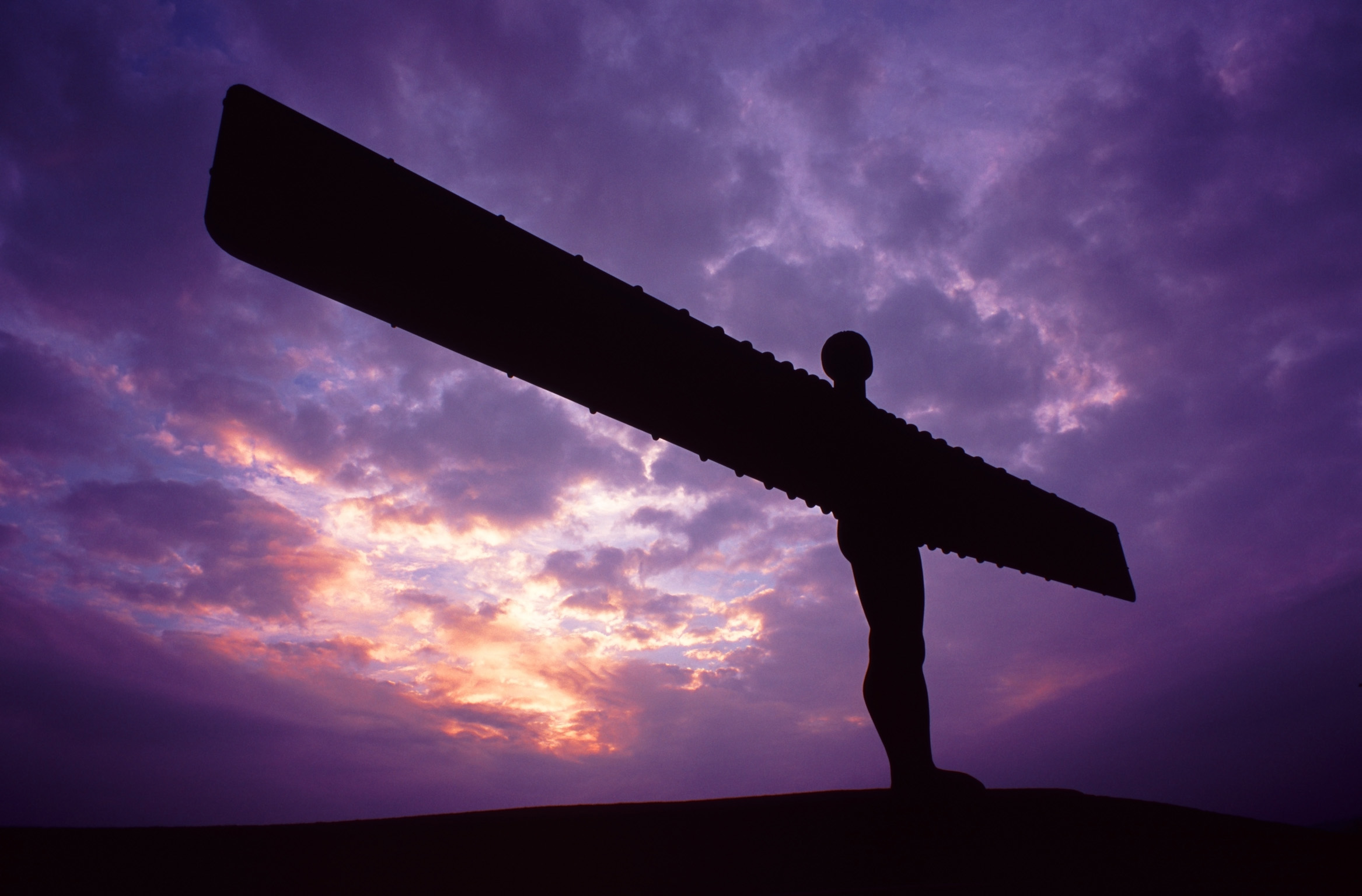 Angel of the North sculpture silhouetted against a colourful purple sky at sunset, Gateshead, Newscastle