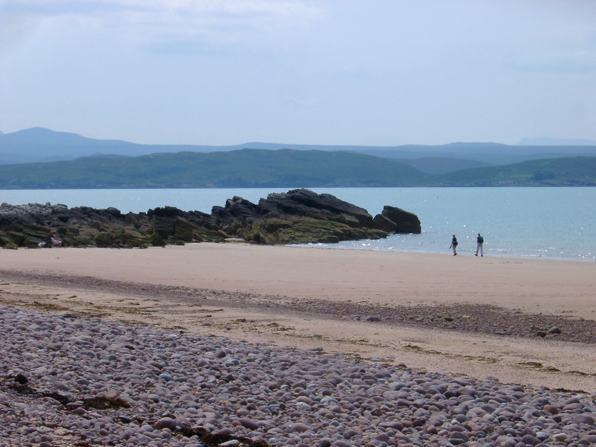 Sandy beach on the shores of Lock Gairloch in the Scottish highlands with people walking along the waters edge in the sunshine