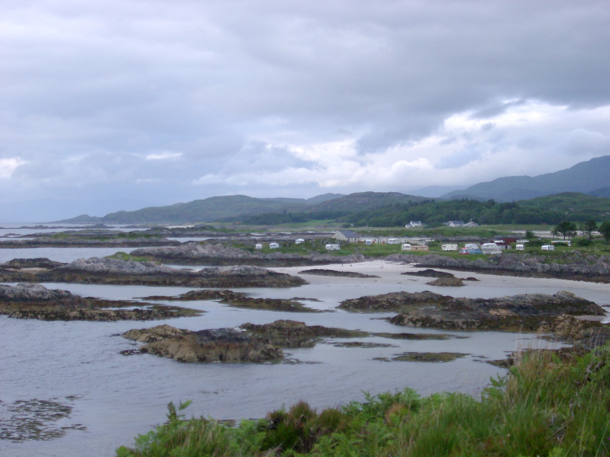 View across coastal grass and stones dotted in shallow water of houses and cottages along the shores of a loch against a moutain background and cloudy grey sky