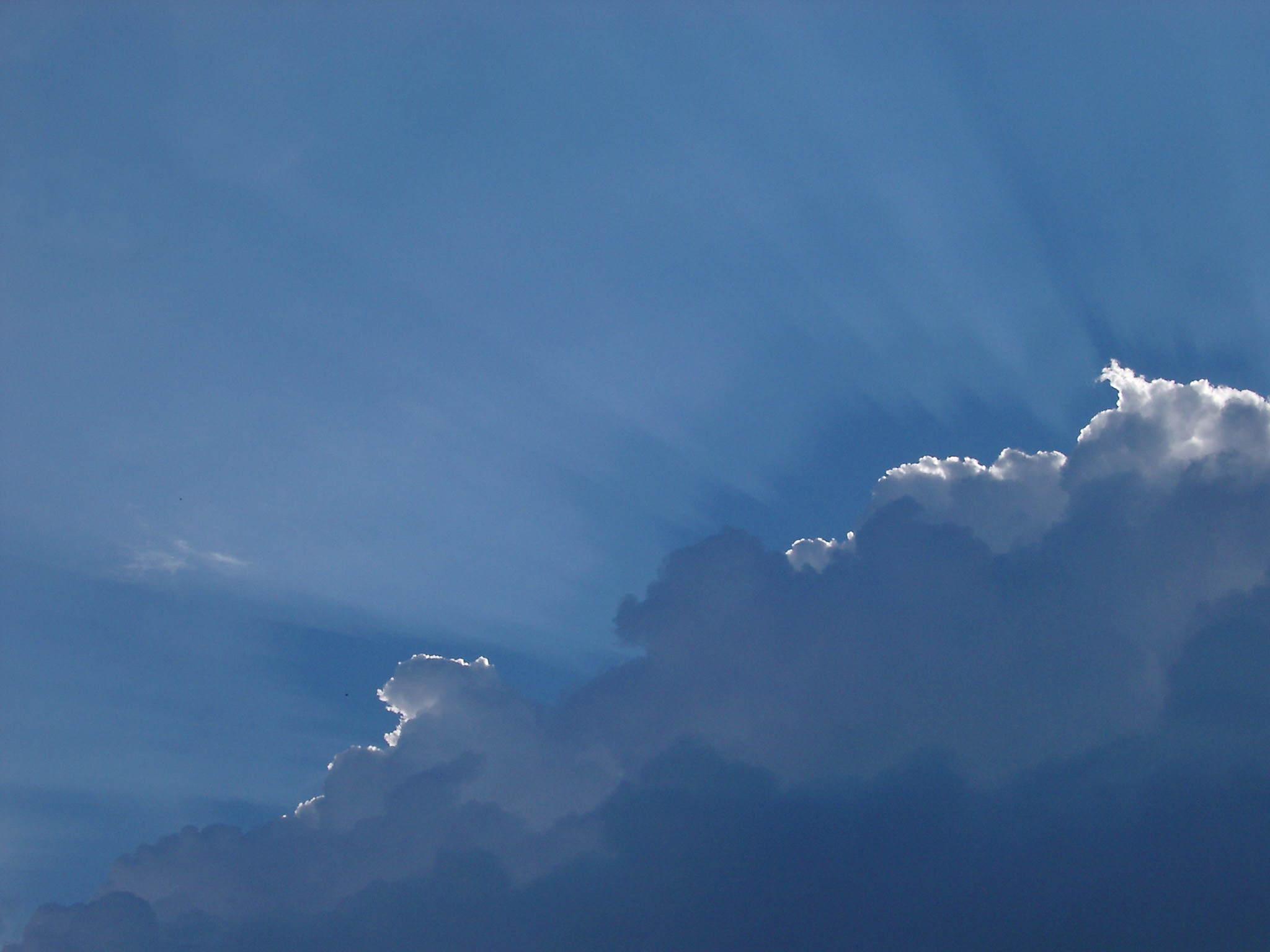Backlit clouds in a blue sky with the suns rays just gilding the top of the formation in a nature and environmental background