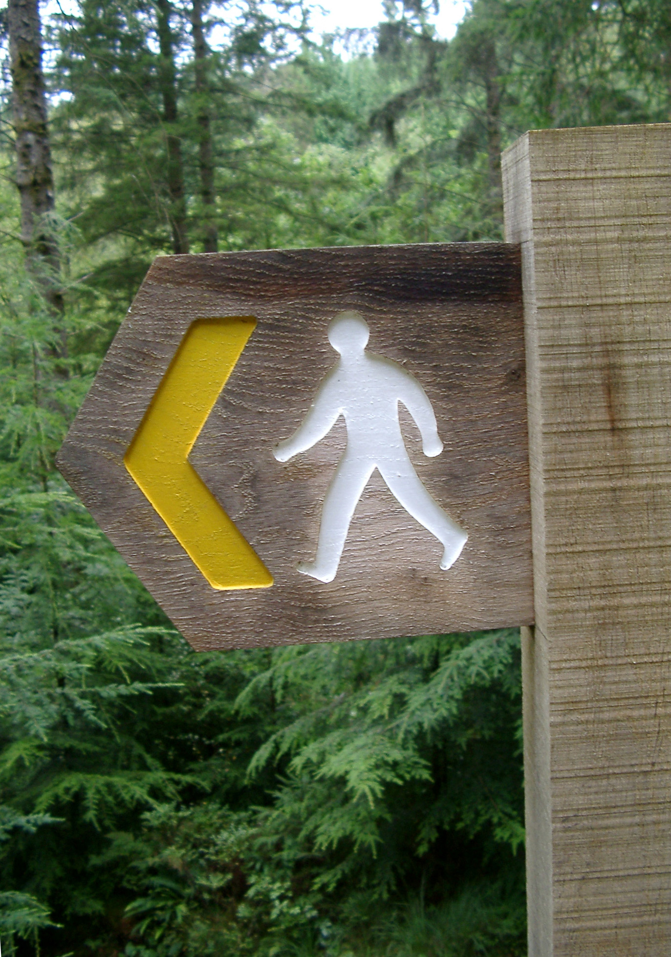Rustic wooden footpath sign with a silhouette of a walking man and left pointing yellow arrow showing the direction of the trail, outdoors in woodland