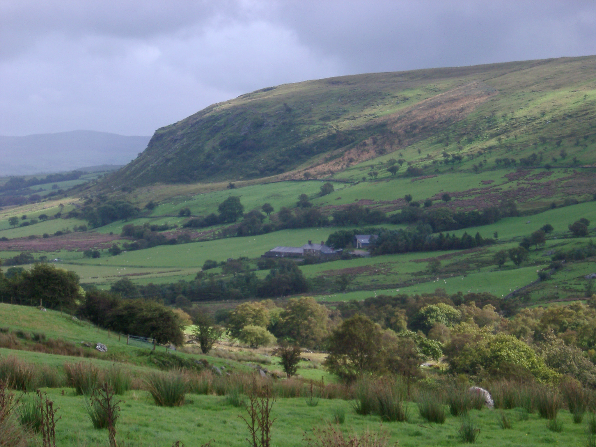 Lush green valley and hill in the Welsh countryside on a wet cloudy day