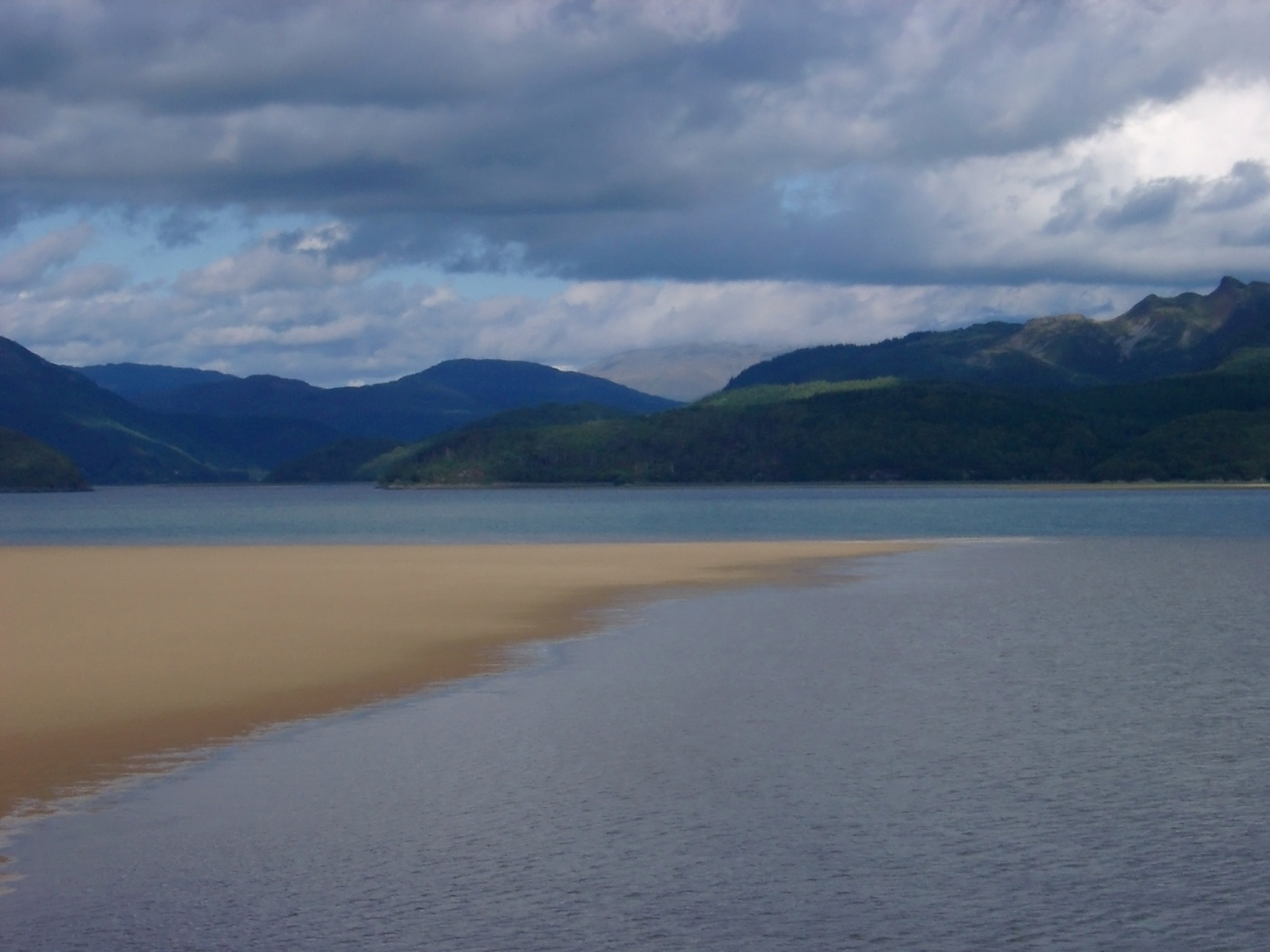 Tranquil Waterside with Brown Sand, Captured with Mountains View