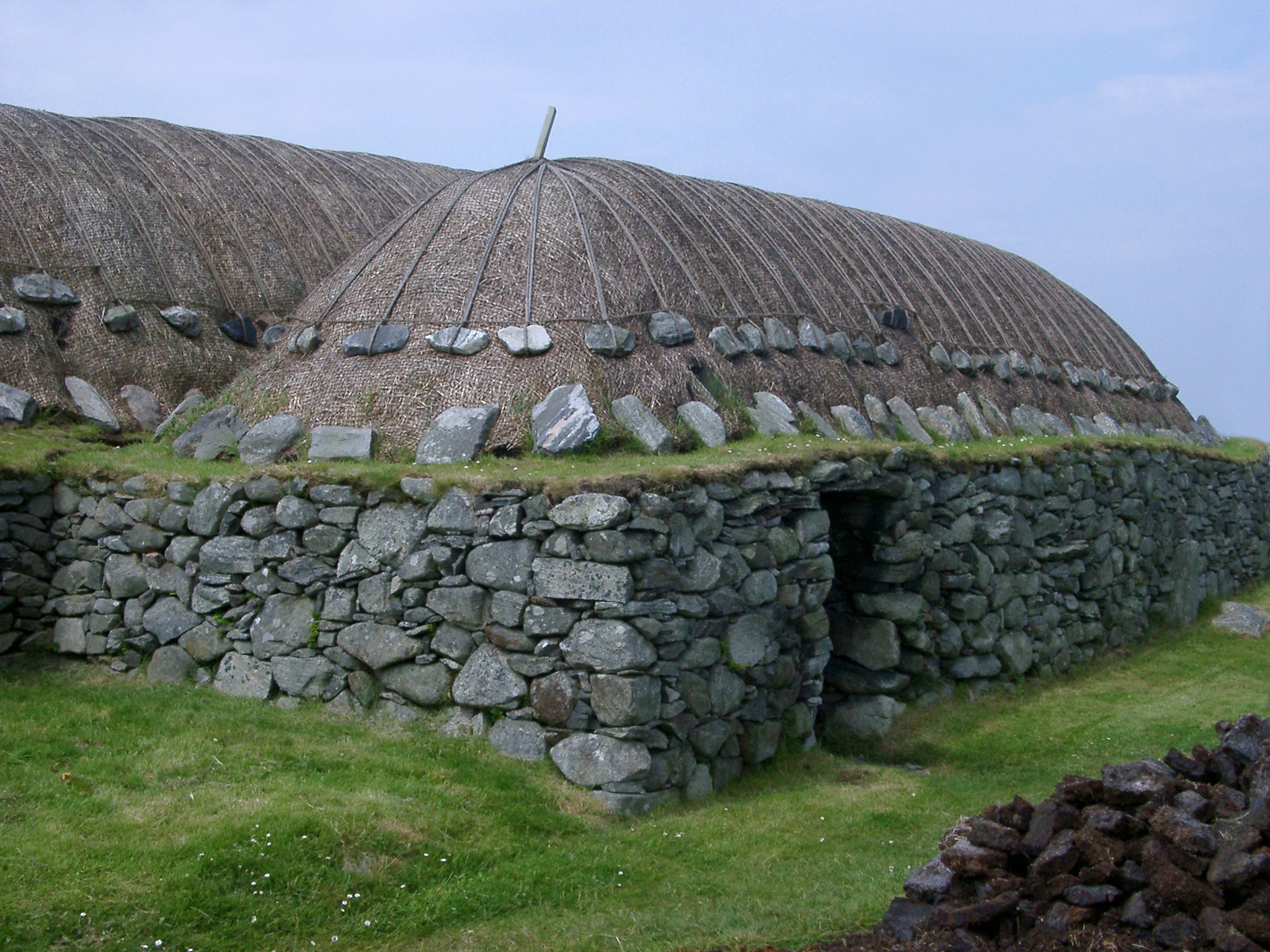 Traditional blackhouse on the Hebrides with its thatched roof and double drystone walls inside which an open fire was built with no chimney so the smoke had to seep through the thatch