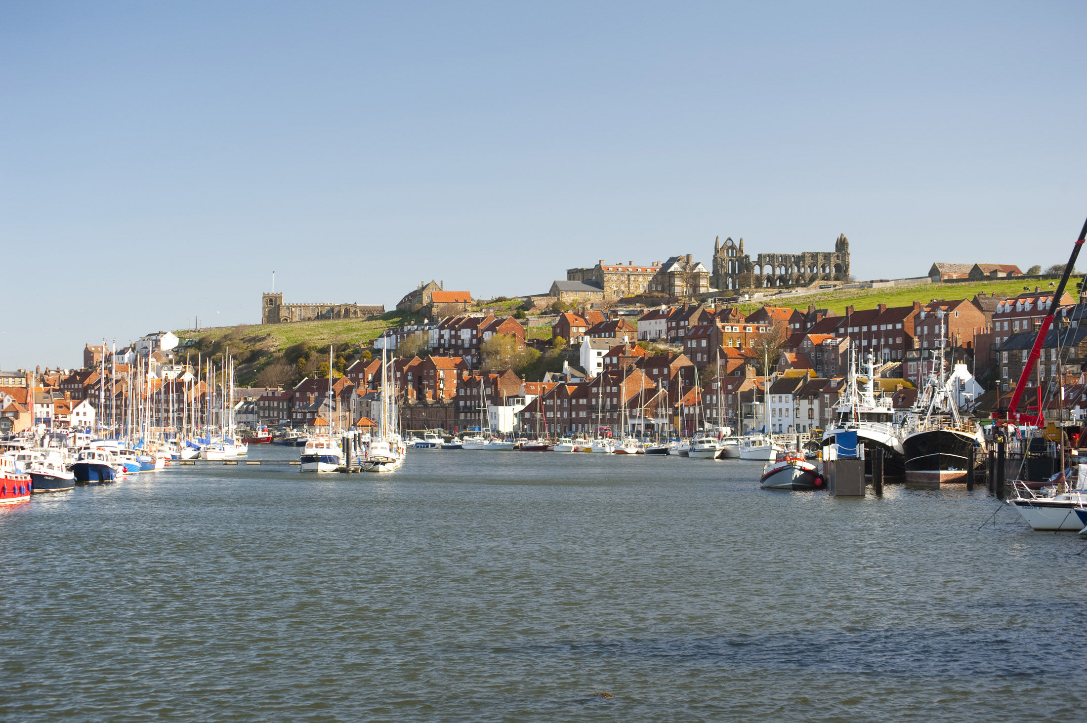 the river esk flowing through the coastal town of whitby with the landmark abbey standing on top of the hill