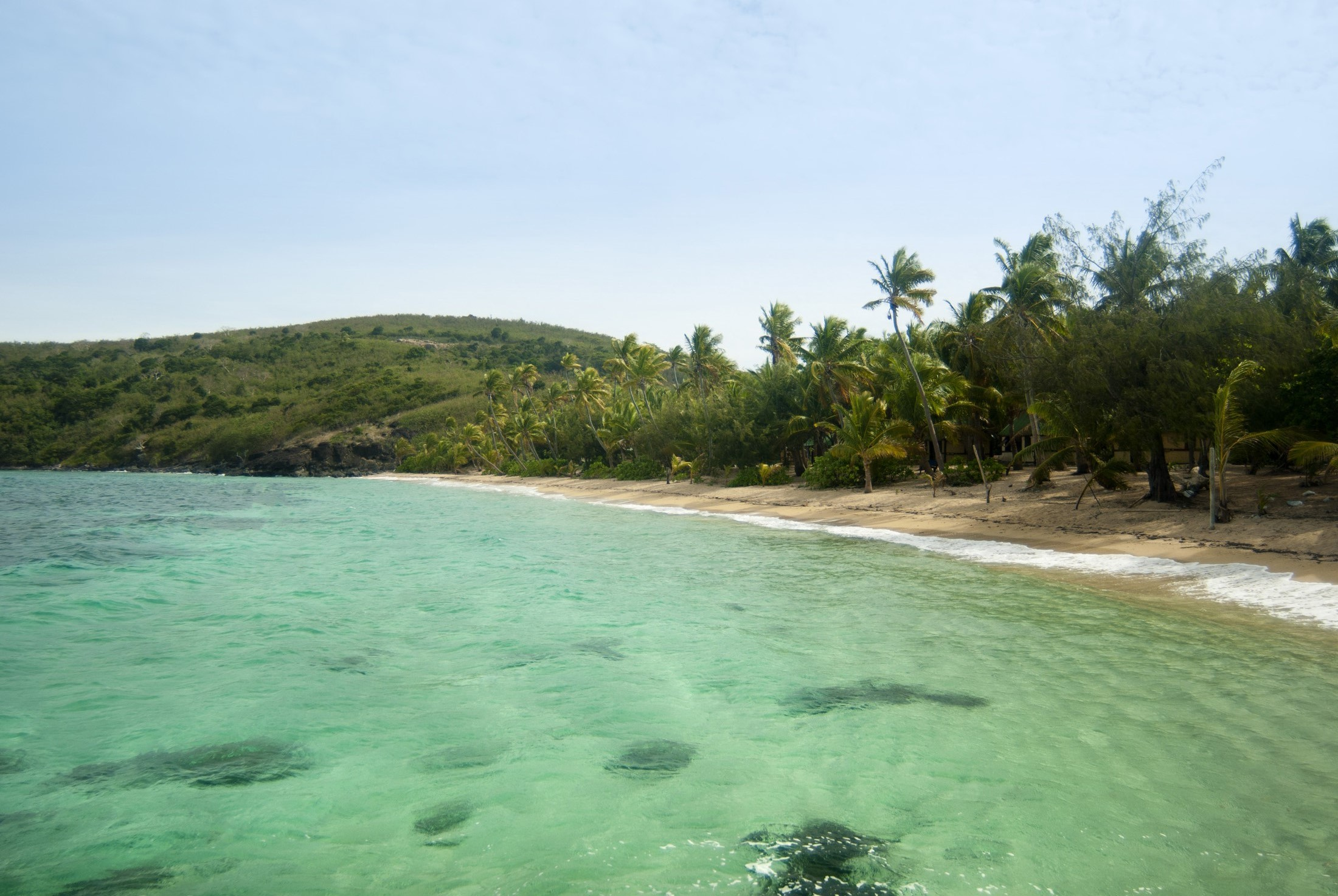 Beautiful clear water in a tropical bay and coastline with sandy beach and backdrop of palm trees