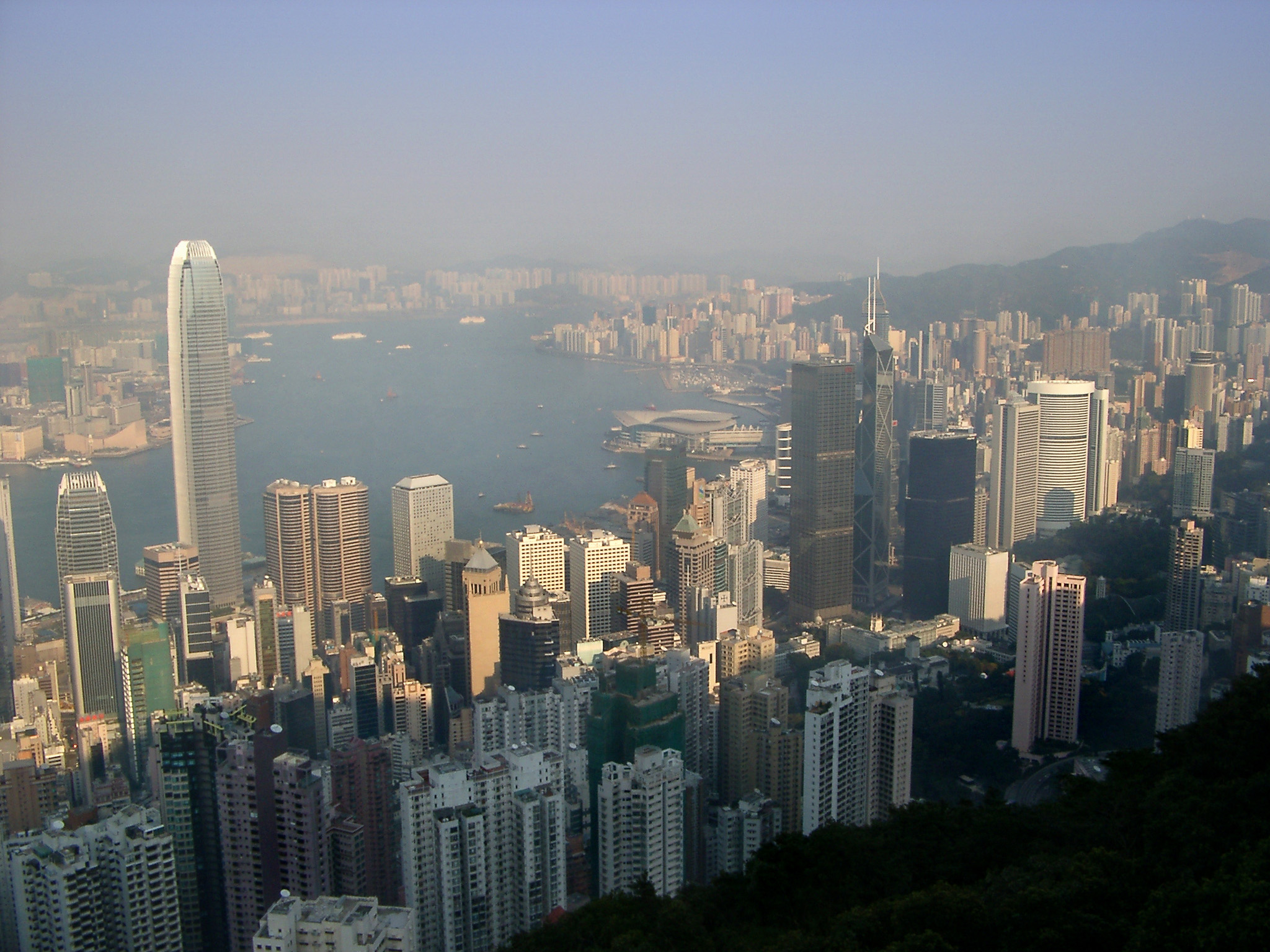 Hong Kong cityscape on a hazy day showing the densely packed modern architecture and skyscrapers with a view out to sea