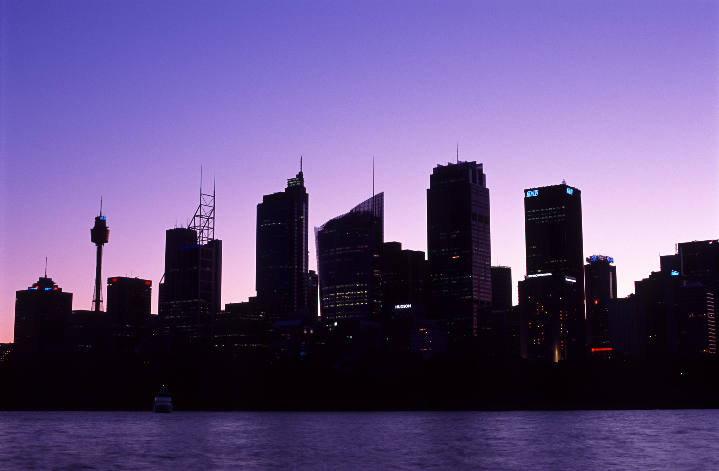Sunset over the Sydney, Australia CBD with the skyscrapers silhouetted against a colorful purple sky at twilight