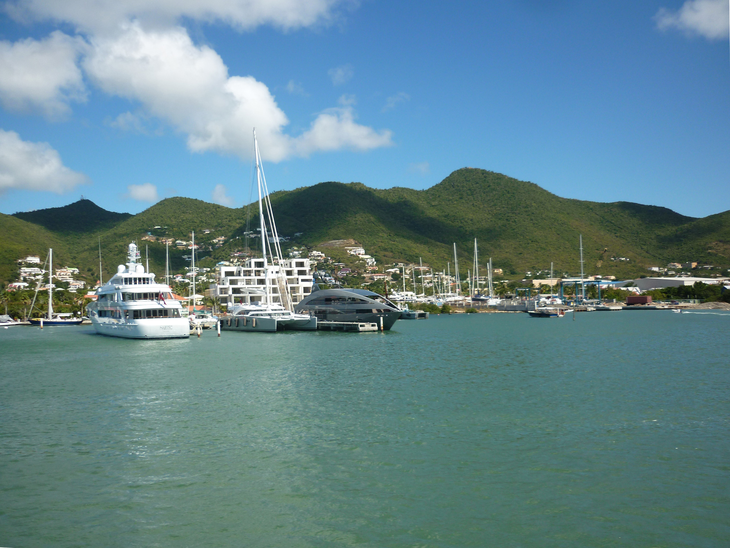 a line of expensive motor yachts, docked at the island of st maarten