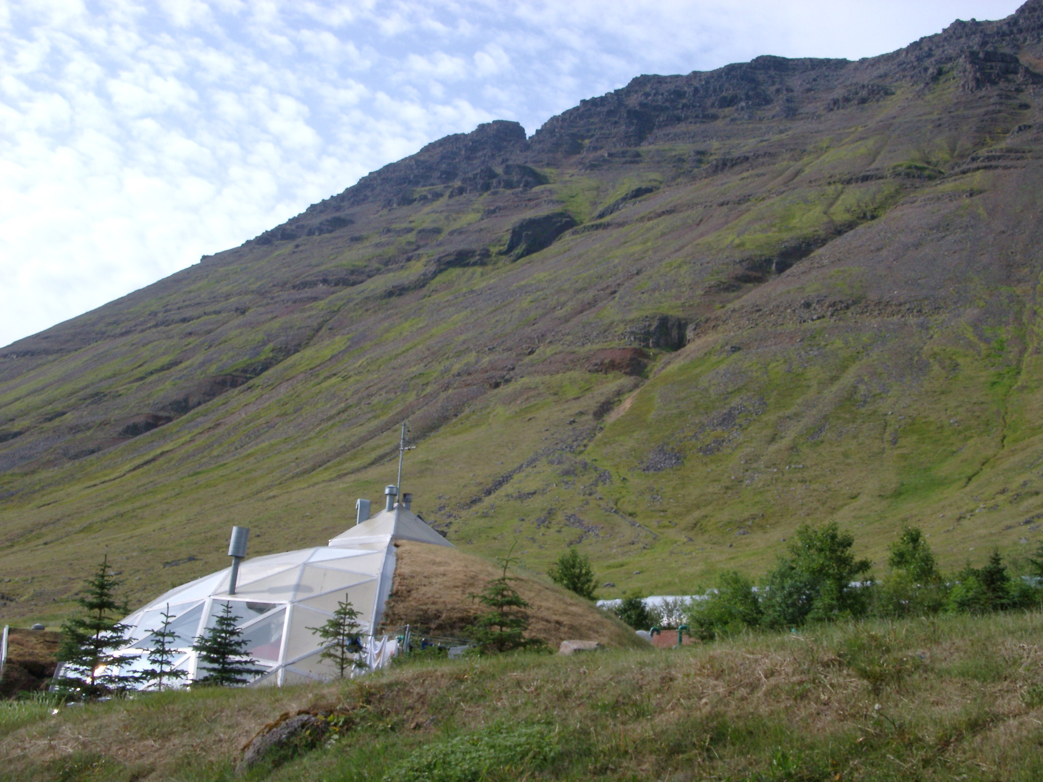 Environmentally friendly biodome, or dome house in Isafjordur in Iceland partially covered in turf built at the foot of a volcanic mountain