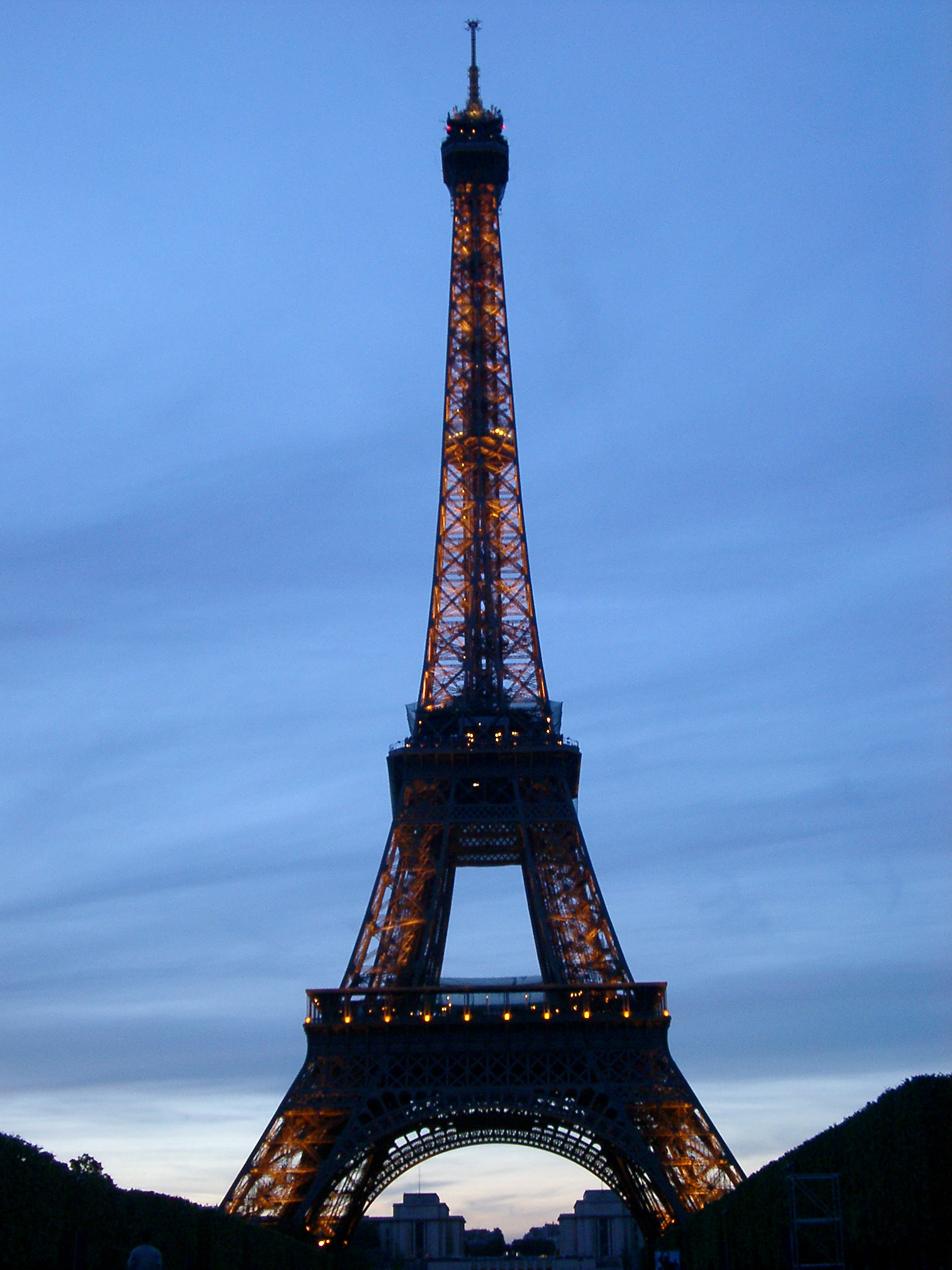 View of the iconic Eiffel Tower in Paris at dusk with the lights illuminated in a travel and vacation concept