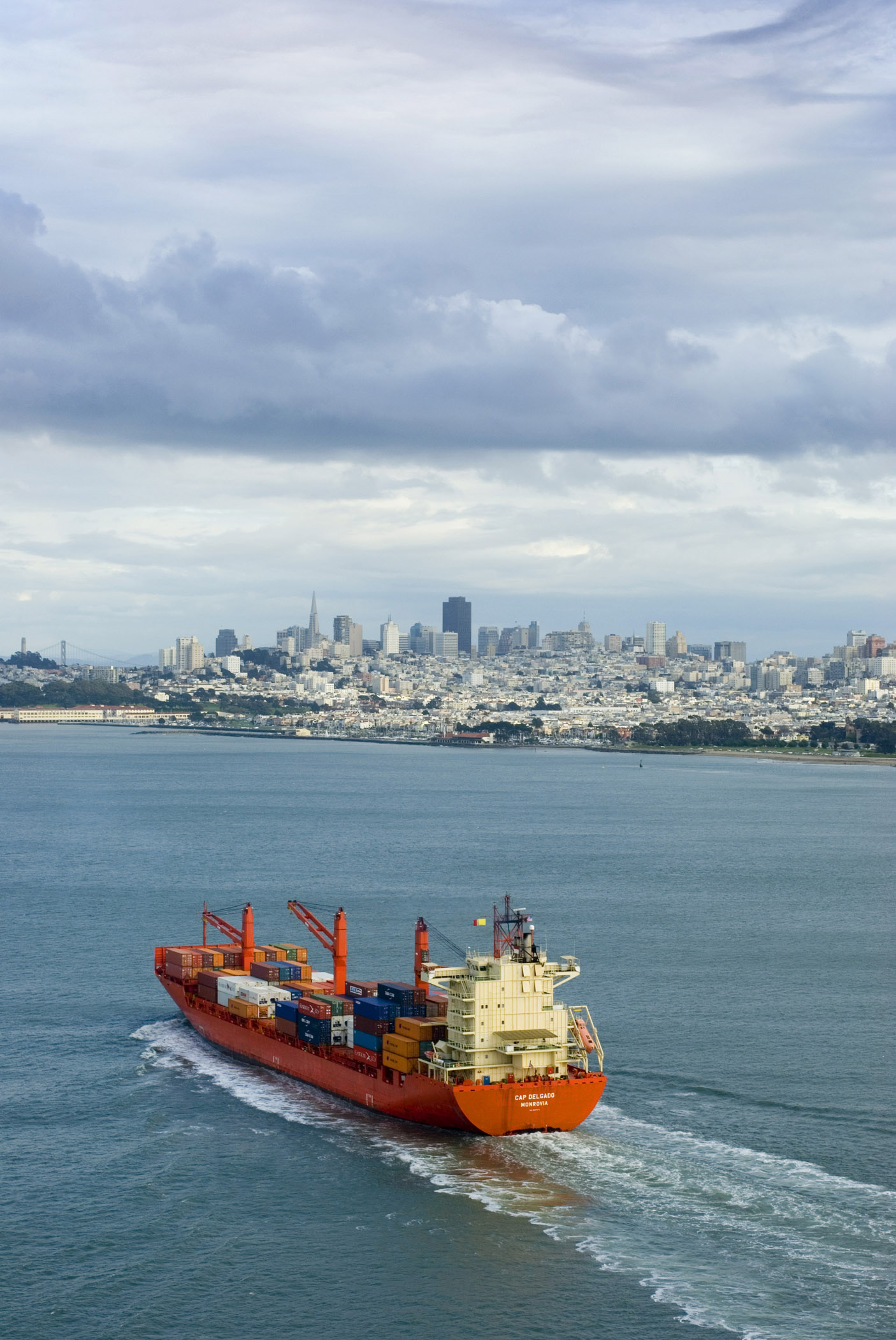 Container ship entering San Francisco bay laden with international cargo containers with the city skyline in the distance