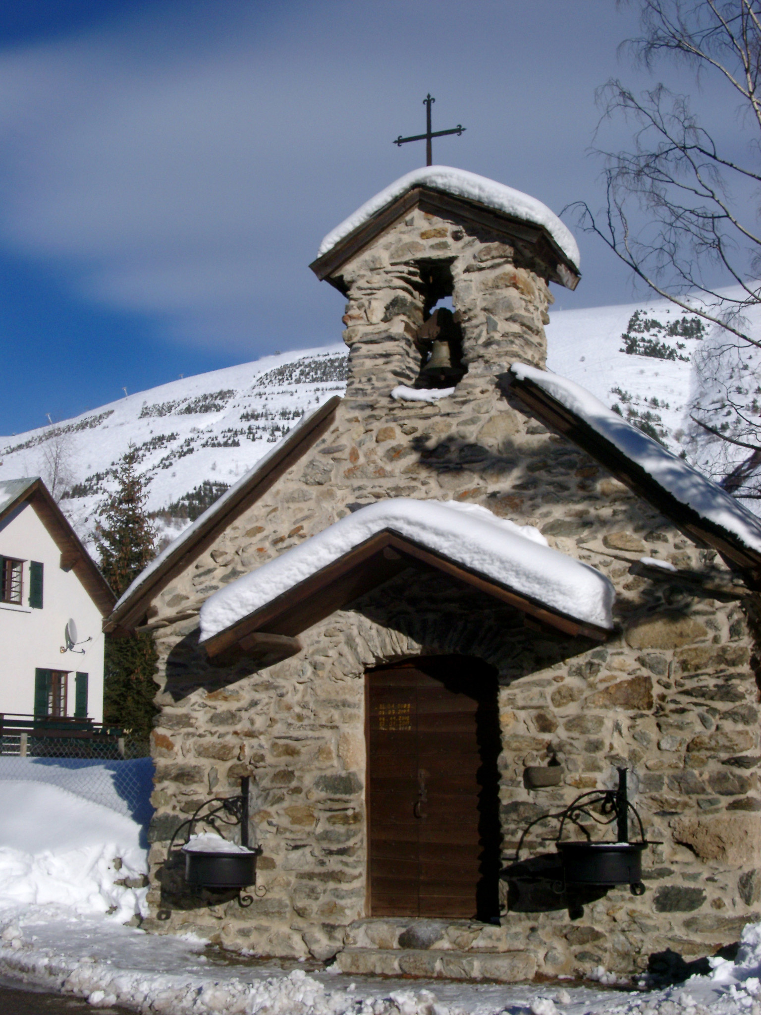 Snows on a Small Historic Alpine Christian Church During Winter Season. Captured with Light Blue Gray Sky Background.