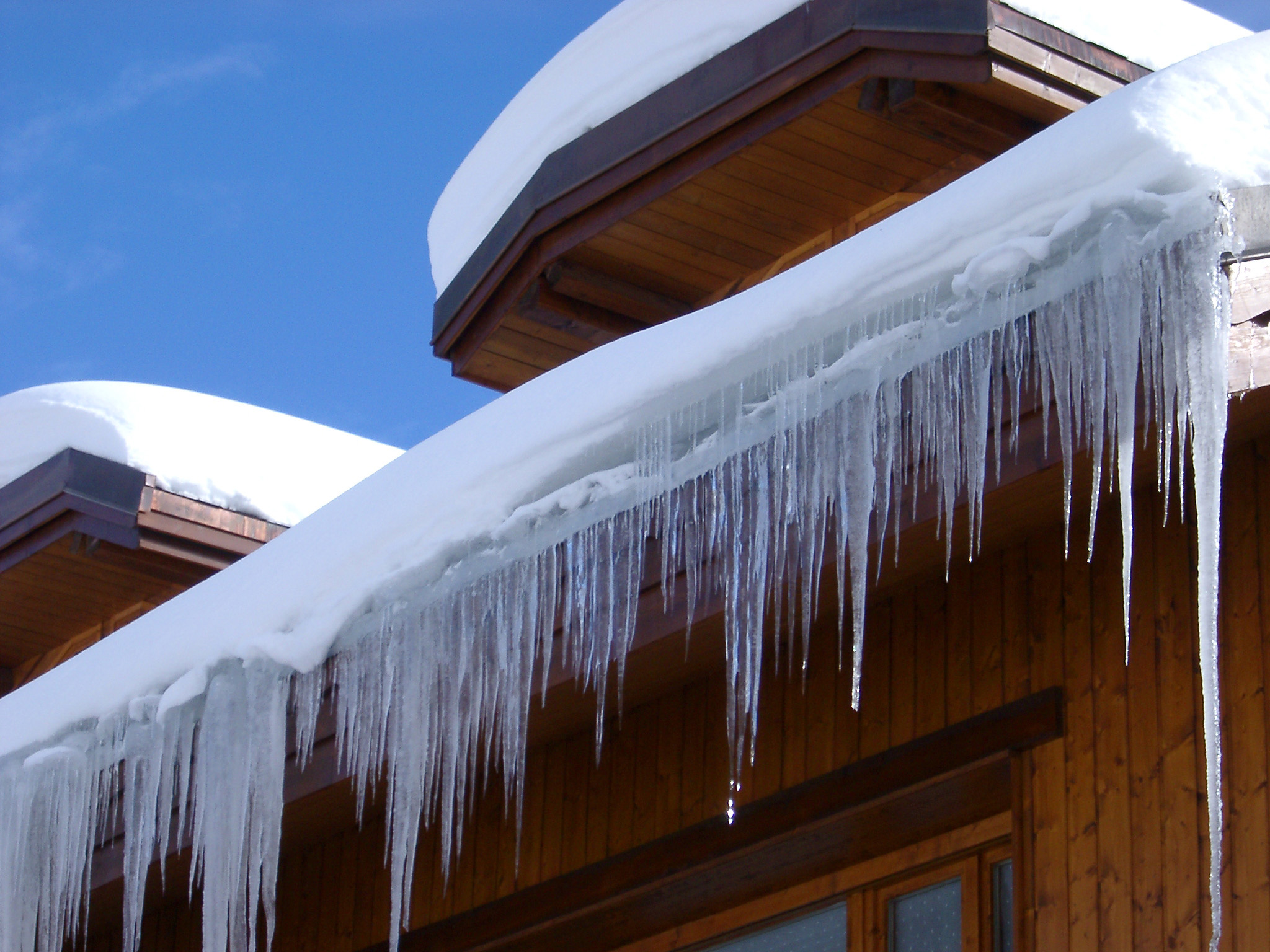 Icicles and a snow covered roof on a winter log holiday cabin against a clear blue sky in a vacation and travel concept